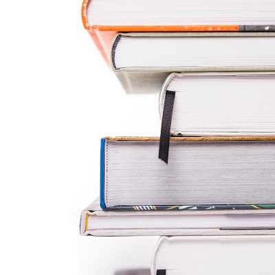coloured books staying on eachother isolated on white